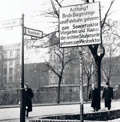 sign says that sidewalk and street belong to the East, while houses and front yards belong to the West Berlin (this was before the Wall was built)