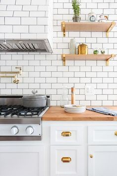 Lovely kitchen features white cabinets adorned with antique brass cup pulls paired with butcher block countertops and a white subway tiles backsplash accented with dark grout.