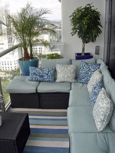 Choosing a color scheme can set the tone for your patio area. HGTV fan bkofficer2 furnished the space with discount blue cushions, pillows and flooring for a high-end look. Different shades of blue are carried through to the oversize planters.