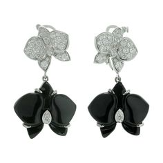 CARTIER Caresse D'Orchidees Diamond Onyx Orchid White Gold Earrings. These delicate Cartier earrings are sculpted in 18k white gold and feature 14.0mm orchids paved with sparkling round E-F VVS2-VS1 diamonds and 18.1mm black onyx orchids set with soliatire brilliant-cut diamonds. A stunning and classic motif in Cartier jewelry. Estimated Diamond Weight is 0.65 Carats.