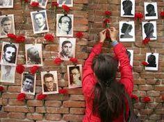 Mujer colocando una rosa en un muro con fotos con victimas del franquismo