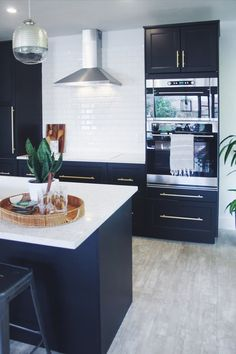 The house was built in 1948 and this was the original kitchen, complete with slanted cabinets, pink tufted leather breakfast bar and metallic butterfly wallpaper. With one less wall and a completely new layout, this renovated black-and-white kitchen shines.