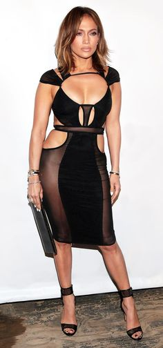 """Photo:  Is Jennifer Lopez the new Benjamin Button?  She sported a black sheer cutout dress by little known L.A.-based designer Bao Tranchi, whose custom creations have also adorned the backs of Rita Ora and Demi Lovato as well as Serena Gomez and Sereyah McNeil in T.Swifty's """"Bad Blood"""" music video. So what makes this look so interesting?"""