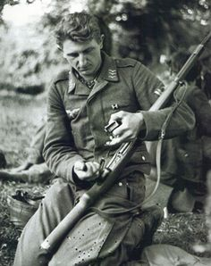 A Fallschirmjager Obergefreiter spotted without his smock cleaning his 7.92mm Gewehr 41 semi-auto rifle in the hedgerows of Saint-Lô, France 1944