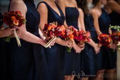 Bridesmaid bouquets with Navy dresses in various styles. Plant material consist fall colored calla lilies, darcy garden roses, pink astrantia,  hypericum berry and ranunculus, Nancy Saam flowers