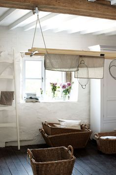 Baskets, dryer, linens, natural beam against white ceiling and wall, contrasted with a more practical dark floor
