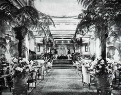 The Winter Garden on the S.S. Leviathan of the United States Lines circa 1923, is set against a background of warm putty color the clustered blossoms and graceful palms in this room provide an almost tropical charm. Soaring columns with gold capitals, chairs and tables painted to blend with the walls, green lattice work and curtains of gold and black, complete and perfect the decoration of this room which is in truth a garden fit either for winter or summer.