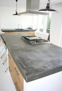 Groot betonnen blad van 10 cm dik zonder naden, donker grijs op ikea kasten met Koak Design houten fronten. www.KoakDesign.nl
