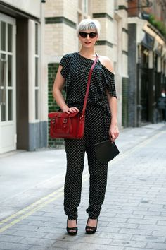 Glamour Hits The Streets – Street Style polka dot jumpsuit with one bare shoulder, red bag, black pumps, sunnies.