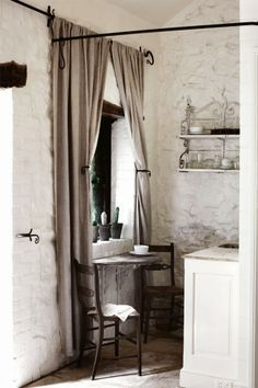 whitewashed stone walls, a half table mounted on delicate scroll work brackets, long linen drapes, all in shades of umber and creamy white-