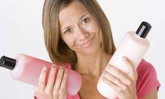 mulher segurando shampoo e condicionador nas mãos