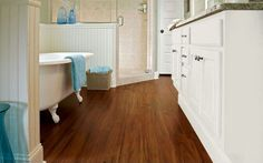 This bathroom offers a classic traditional look. Its simplicity is achieved through white cabinetry and bead boarding, a wood-look bathroom flooring and pops of color. Since real hardwood flooring can be damaged by water and humidity in bathrooms, a wood-look vinyl plank flooring or laminate are great alternatives.