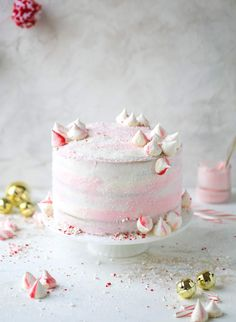This pink peppermint cake is festive and delicious for the holidays! Layers of vanilla cake frosting with peppermint cream cheese frosting, covered in sparkly sugar and peppermint meringues. Couldn't be cuter! I #pinkpeppermint #cake