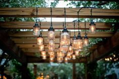 I love the homemade mason jar lights hanging from the pergola. Now I just need some jars and lights and pergola wood. Dan take note, happy wife happy life Restaurant En Plein Air, Outdoor Restaurant, Restaurant Lighting, Pergola Lighting, Outdoor Lighting, Exterior Lighting, Outdoor Chandelier, Dramatic Lighting, Pergola Patio