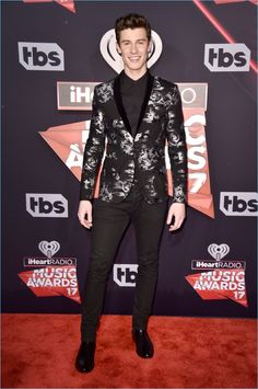 Shawn Mendes dons a black silver brocade shawl collar dinner jacket from Emporio Armani. The singer also wears a black shirt and trousers from the Italian label.