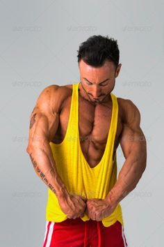 Muscular man pulling down tanktop on torso ...  adult, arms, athlete, athletic, attractive, beautiful, body, bodybuilder, caucasian, chest, down, fit, fitness, guy, handsome, healthy, hot, hunk, macho, male, man, masculine, model, muscle, muscleman, muscular, person, portrait, posing, pulling, sexy, shirt, smile, standing, strength, strong, tan, tank-top, tanktop, torso, white, young