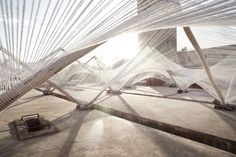 Red gigante en Marrakech. La instalación del hilo de araña. Bajo el título 'Telar-hiperbólica', la obra de sitio específico en el recinto de la mezquita de Koutoubia, está inspirado en la artesanía de tejer marroquí y la geometría de la arquitectura Marrakech. La estructura - formado de la madera del pino pelado a mano locales - se hace eco de la forma del telar de madera tradicional, y crea un efecto dosel 'hiperbólica' una vez que el hilo se ha estirado sobre sus cuadros.