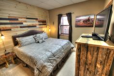 Sasquatch Ridge Pigeon Forge vacation rental cabin - Horse Room on lower level has king bed with memory foam mattress, hand made side tables made of logs and tree slabs, a log dresser, television and a wood accent wall.