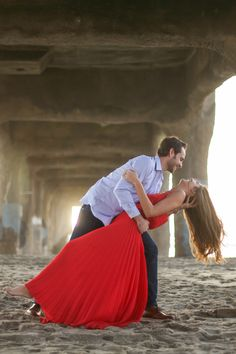 Adorable beach engagement photo. I love the low dip pose and her red dress. Engagement photography | beach engagement photos | couples photos