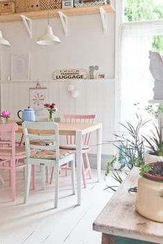 Caroline's Joseph Dining Table in Oak and White, Pastel Chairs, White floorboards and pretty green plants. The perfect light pastel kitchen.   MADE.COM/Unboxed