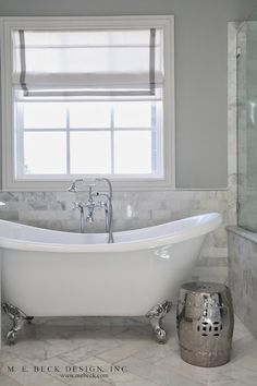 Stunning bathroom features a silver claw foot tub paired with a vintage tub filler with hand shower situated below a window dressed in a gray grosgrain trimmed roman shade framed by gray paint on upper walls over Carrara marble brick tiled lower walls alongside silver garden stool atop Carrrara marble herringbone tiled floors.