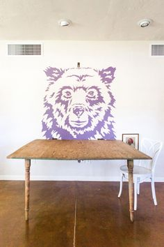 Bjorn collaborated with local artist, Kelly Driscoll to create this convertible dining room table area. The purple bear is Eggplant from Dunn Edwards. The table is convertible. When it's not in use it flips up and latches to the wall with bracket above bear to create more space, and the legs collapse against table to create art piece when latched to wall.
