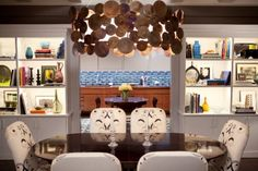 How awesome is this dining room?  I love the chandelier (could maybe DIY it with wood circles?), and the lighting in the bookcases is perfect and it really adds life to the room.  I'm also loving the blue Ann Sacks tile in the kitchen.