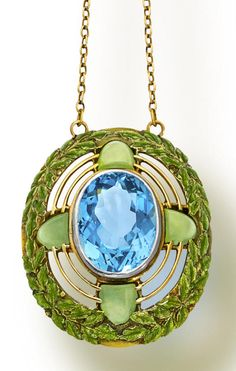 An arts and crafts aquamarine, chrysoprase and enamel pendant necklace, Tiffany & Co., circa 1910. Centering an oval-cut aquamarine, within an openwork surround, enhanced by green enamel foliate motifs, detailed with cabochon chrysoprase, suspended from a fancy-link chain; signed Tiffany C. for Tiffany & Co.; mounted in eighteen karat gold; length 17in.; pendant length: 1 1/2in. Via Bonhams.