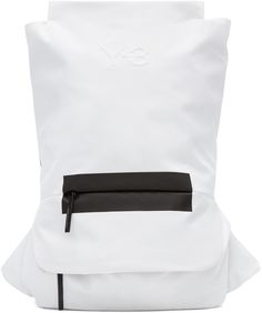 Unstructured textile backpack in white. Faux-leather trim in black in black throughout. Adjustable padded shoulder straps. Adjustable waist strap featuring zippered pocket. Embossed logo and zippered pockets at face. Padded panel at back. Zip closure at main compartment. Padded laptop compartment at interior. Textile lining in black. Black hardware. Tonal stitching. Approx. 13