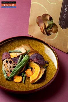 麻布野菜菓子 野菜チップス[あじ塩、カリー、果物]  東京スタイル。和の中の洋 味わいも見た目もスタイリッシュ。野菜で作ったちょっと贅沢な新・野菜スウィーツ。麻布野菜菓子。  短時間に野菜の水分を蒸発させる減圧フライ製法で、野菜の本来の色と風味をそのままに、カリッとサクサクっとしていて、油で揚げたとは思えないほどさっぱりと仕上げています。野菜の形と色を残しながら、口に放り込めば素材そのままの食感。チップスとしては珍しいオクラなどもあり、ひと口食べてみるとほのかな粘りも残っていて、新食感を堪能することができます。  東京スイーツの激戦区のひとつの麻布ブランド。和の中の洋のテイストの野菜菓子。味わいも見た目もスタイリッシュ。美容健康に注目。食物繊維がたっぷりでメタボ予防にも。健康面だけでなく、味わいもデザートとしても上質。東京のスタイリッシュな包装でご贈答用 ギフトにもぴったり。
