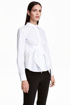 Chemise avec ceinture à nouer: Chemise en tissu de coton léger avec ceinture à nouer à la taille. Modèle avec col rabattu et boutonnage dissimulé devant. Empiècement d'épaules flottant dans le dos et manches longues terminées par poignet boutonné. Découpe à la taille avec basque légèrement évasée.