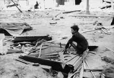 Boy squatting on remains of a piano during the Warsaw Uprising occupied Poland 1944 [1024x704]