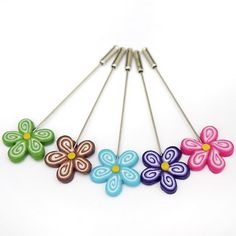 Alfileres de pasta con forma de flor con cinco pétalos en colores alegres y llamativos para regalar en una ocasión especial a tus invitadas