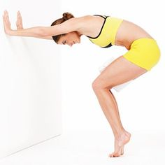 """C-Curve: Stand facing a wall w/ legs together, squeezing rolled-up towel btwn thighs. Hinge forward at hips, knees slightly bent, to flatten palms against wall so back is nearly parallel to floor. Squeeze abs & towel as you rise onto toes, and do 20 pulses by raising hips 1"""" then lowering hips 1"""". 3 Sets. (7 Waist-Slimming Ab Exercises)"""