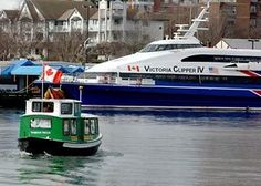 A water taxi cruises past the Victoria Clipper, docked in Victoria's Inner Harbour.