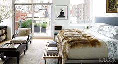 In this master bedroom, the sheets are by D. Porthault, the coverlet is by Ankasa, and the coyote throw is by Pologeorgis. The bench is by George Nelson, the armchairs are by A. Rudin, the photograph of Marilyn Monroe is by Bert Stern, and the rug is by Custom Cool Rugs. Tour the entire home.