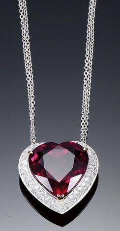 RUBELLITE AND DIAMOND NECKLACE. Centring on a heart-shaped rubellite weighing 24.99 carats to a millegrain and pavé-set border of brilliant-cut diamonds, on two fine chains, length approximately 430mm.