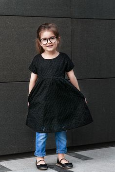 Miss Kaira wearing edgy black dress over jeans and Sons + Daughters Clark frames