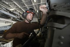 U.S. 5TH FLEET AREA OF RESPONSIBILITY (Oct. 5, 2013) Aviation Electrician's Mate Airman Kevin Williamson, from Atlanta, assigned to the Wolf Pack of Helicopter Maritime Strike Squadron (HSM) 75, uses a grease gun on the tail-disconnect of an MH-60R Seahawk helicopter in the hangar bay aboard the aircraft carrier USS Nimitz (CVN 68). (U.S. Navy photo by Mass Communication Specialist Seaman Derek Harkins/Released)