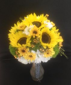 Sunflowers take center stage in this bouquet which also includes Viking mums that look like mini sunflowers. White hydrangeas, frilly green dianthus, and orange wax flower are complete the look.  See more wedding bouquets, centerpieces, and more at www.jeffmartinsweddings.com