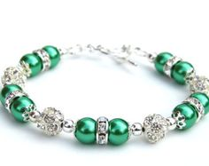 Apple green pearls and sparkling rhinestones make this a shimmering gift or bridesmaid accessory.  I have strung 10mm and 8mm glass pearls with 8mm rhinestone fireballs and rondelles. The bracelet measures 7.5/19cm and is finished with a silver plate toggle clasp. If you need the length of the bracelet adjusted, leave a note of the length needed in the message to seller.  Like this bracelet but prefer a different colour? Check out my other bling pearl bracelets here…