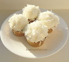 Coconut White Chocolate Snowball Cupcakes light coconut cupcakes topped with white chocolate whipped buttercream and covered in sweetened coconut with added sparkle. A perfect festive bake that can be eaten all year round!