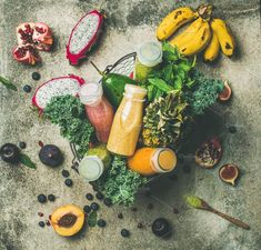 #Colorful smoothies in bottles  Colorful smoothies in bottles with fresh tropical fruit and greens in basket on grey concrete background top view. Healthy vegetarian detox dieting clean eating breakfast food concept