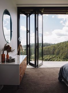 Floating vanity acting as a dresser as well, round mirrow, accordian glass doors, and a view to die for in this home's bedroom