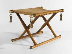 folding stool - x-frame design — a pin acting as a hinge between two crossed slats with animal skin or fabric stretched across the top for a seat