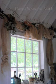 She uses slim branches as curtain rods, weaves ivy through and adds inexpensive burlap from Lowes.  A little birdsnest on top makes it perfect!  Home is where the Boat is Blog.