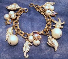 Mid Century beach ocean theme charm bracelet •Sea horse, starfish and sea shell charms, with faux pearls attaches •Dangling faux pearl beads, and aurora borealis rhinestone charms •Fish and shell charms have a light white wash irregularly applied •Gold tone chain is 7 1/4 inches long, figural charms are about 3/4 - 1 1/8 inches •Unsigned •Very good vintage condition, shows minimal wear •International buyers welcome, shipping is automatically combined, overcharges are refunded •...