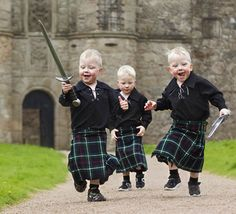 Three-year-old triplets Jack, Cameron and Liam Noble get in on the 'Brave' act with kilts and toy swords.  Tolquhon Castle, Scotland.