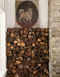 Firewood is stored beside the dry-stacked stone fireplace. The top row of logs is actually mounted to the wall to form a shelf.