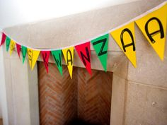 """A Colorful Kwanzaa: Dress your dining room with the colors of Kwanzaa: red, green and black. Adorn a mantle with a simple garland that conveys the traditional holiday greeting, """"Joyous Kwanzaa!"""" To make your own, cut triangles from colored card stock and draw each letter in black. Attach to ribbon by hot-glueing card stock to bottom half of ribbon, then fold ribbon over and secure with glue."""